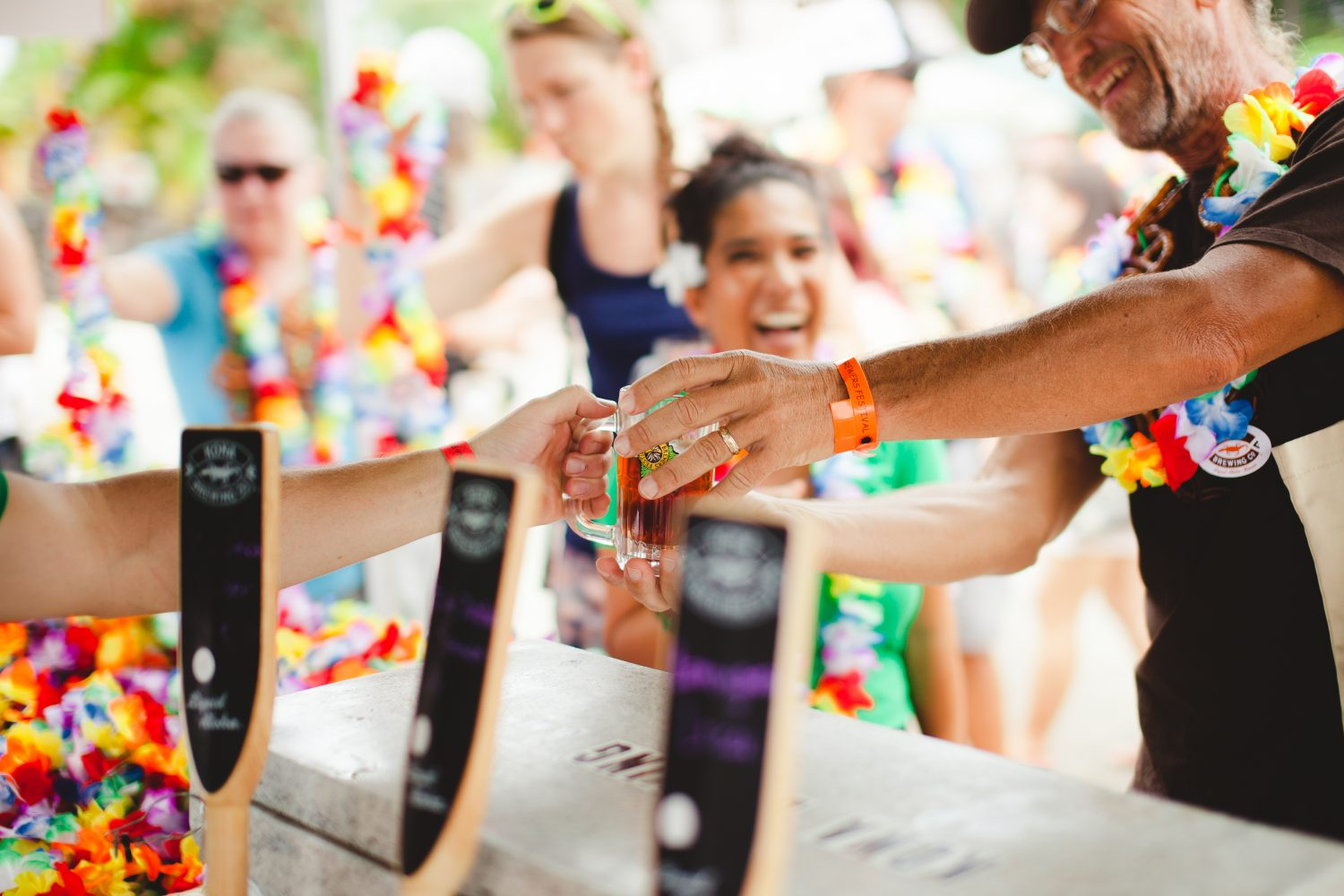 kona brewers festival people grabbing glasses of beer from enthusiastic pourers. credit goes to the kona brewers festival and couple cups for this photo