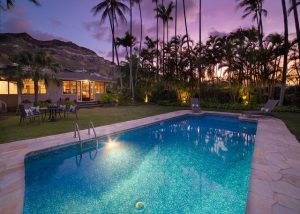 pool next to house in front of mountains, palm trees, and purple sky