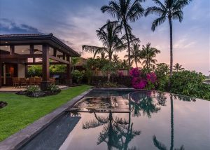 vacation rental with pool, palm trees, and colorful sky